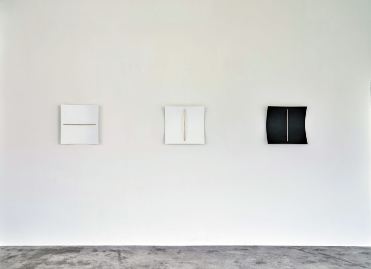 """LEFT: """"1:1 Resonance, horizontal"""", 2021, Wooden panel, painted in white; polished brass beam; beater, 47 x 50 x 9 cm ; CENTER: """"1.37:1 Resonance, vertical"""", 2021, Wooden panel, painted in white; polished brass beam; beater, 47 x 66 x 8,5 cm ; RIGHT: """"1.1 Resonance, vertical (black)"""", 2021, Wooden panel of 50 x 50 cm, painted in black; Polished brass beam of 40 x 0,6 cm, beater, 47 x 50 x 9 cm"""
