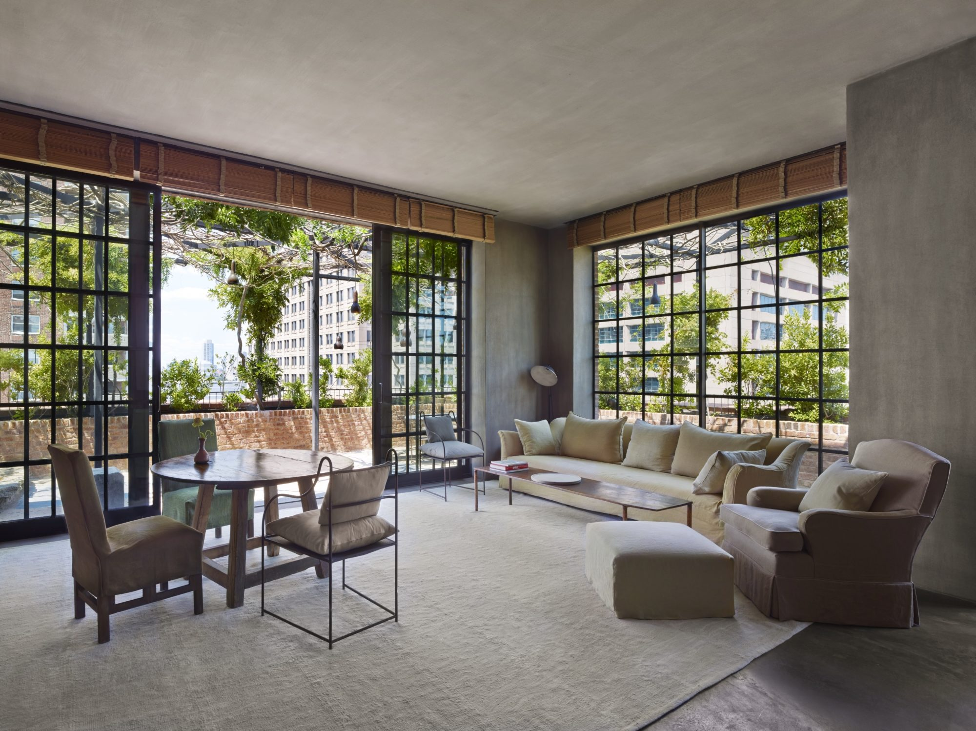 Indoors meets the outdoors with a view of the sitting room and terrace in TriBeCa at New York's Greenwich Hotel