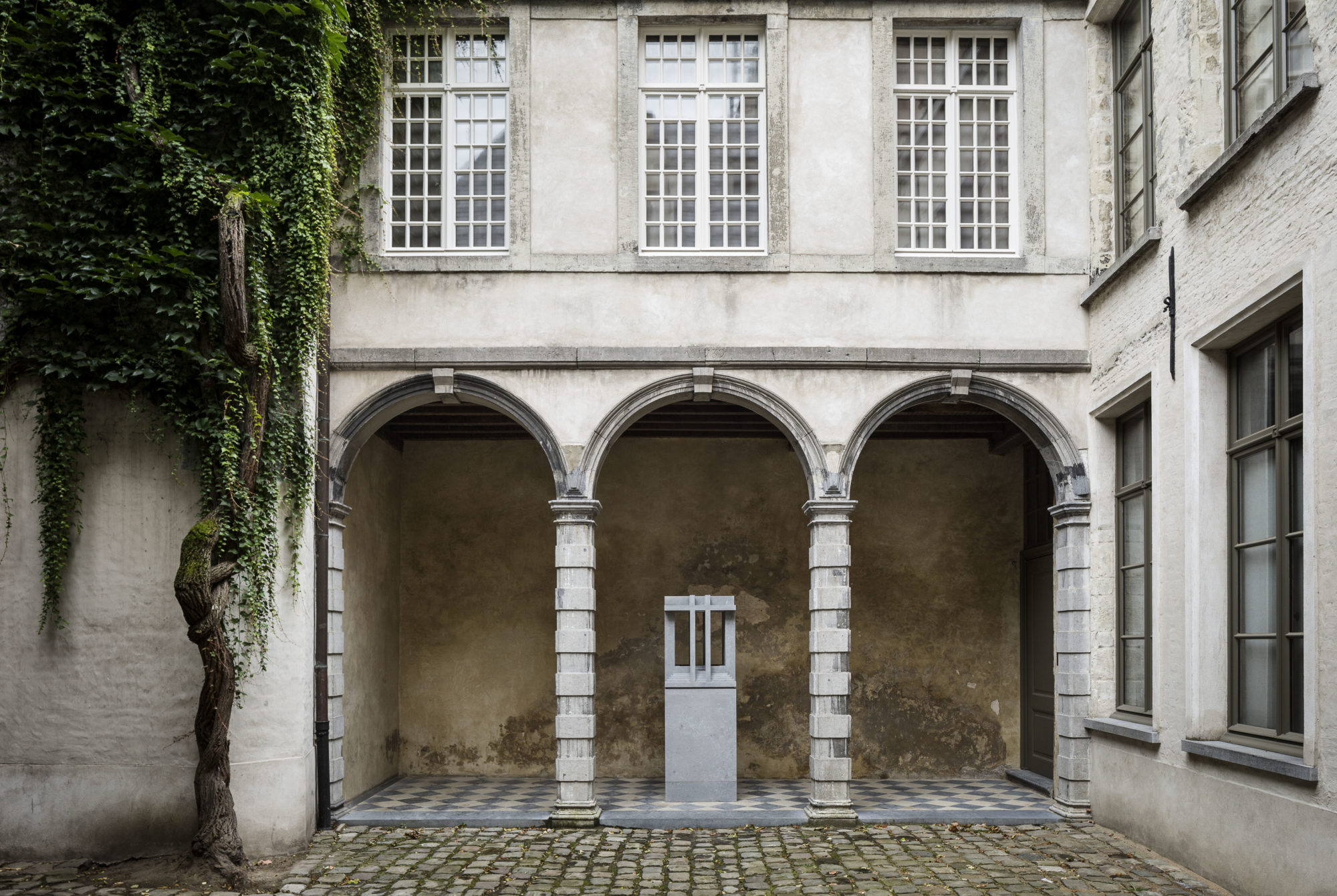 A view of the Vlaeykensgang's central courtyard with historic columns and an artwork by Renato Nicolodi